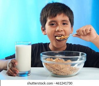 latino boy eating cereal isolated on blue background