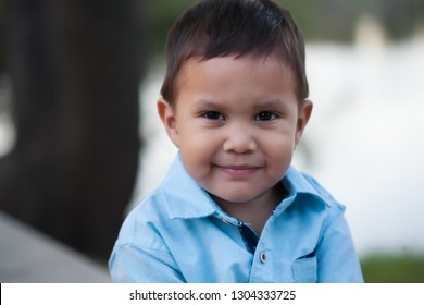 Latino boy wearing blue shirt and a thoughtful look,  with a relaxed smile but also looking uncertain.