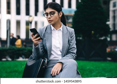 Latino businesswoman checking mobile notification on modern cell smartphone, Hispanic female CEO using digital phone for search contact number or data info during work break at urban setting