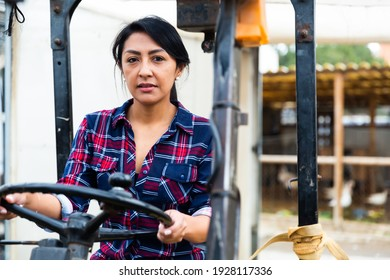 latino colombian woman forklift worker operator driving vehicle at warehouse