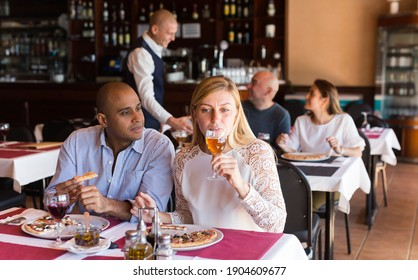 Latino couple in love eating pizza at cozy restaurant