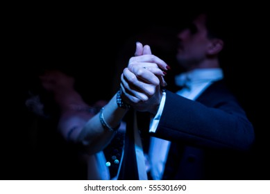 Latino dancers in ballroom  on black background. focus on hands