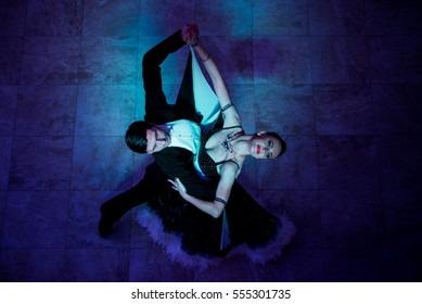 Latino dancers in ballroom  on black background.