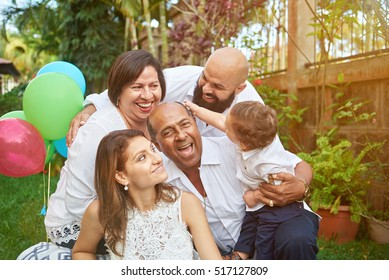 Latino family have fun on garden with small son kid boy