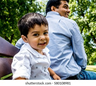 Latino father and son sitting outside on a bench