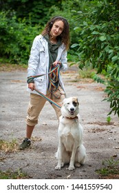 Latino girl with dreadlocks keeps a dog on a leash. Green blurred background. Communication with the animal. Summer day.
