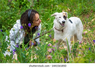Latino girl with dreadlocks sitting next to a dog. Green blurred background. Flowers in the foreground. Summer day. Communication with animals.