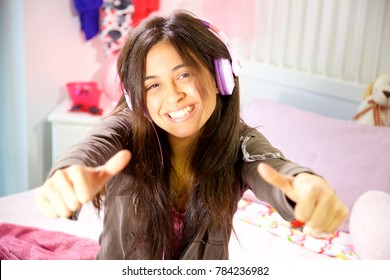 Latino girl sitting in bed listening music