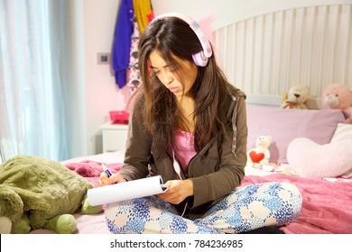 Latino girl sitting in bed writing