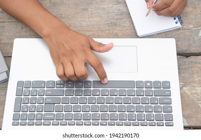 Latino hands using a computer. Brown fingers typing a laptop. Laptop keyboard being used by Latin hands. Horizontal imagen.