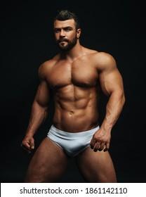 Latino hunk in white swimwear at black background in studio