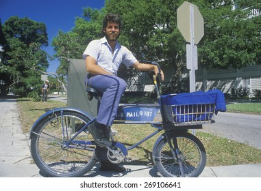An Latino mail carrier bicycling on his route, St. Petersburg, FL