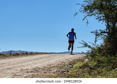 Latino man running a race on a rural road during summer. Crosscountry race. Copy space.