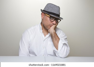 Latino Man wearing a gray hat and glasses is falling sleep