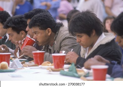 Latino men eating Christmas dinner at homeless shelter, Los Angeles, California