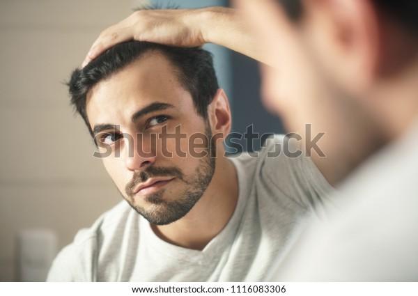 家では、あごひげを生やしたラテン系の人が浴室でグルーミングをしている。髪の毛の喪失を心配し、遠く離れた髪の線を鏡で見ている白人のメトロセクシュアル男性。