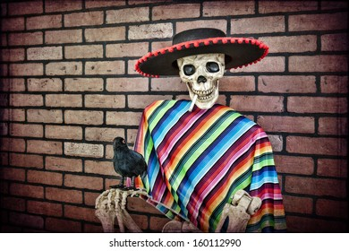 Latino skeleton sitting against a brick wall having a smoke with his trusty pet crow.