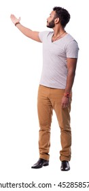 Latino young man with beard pointing behind. Full length portrait. Isolated on white background.