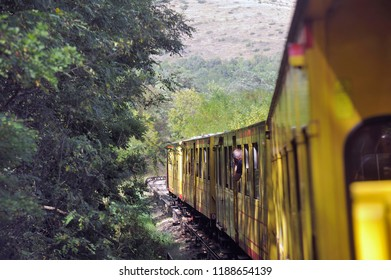LATOUR DE CAROL, FRANCE - SEPTEMBER 4, 2018: The small yellow train of the Pyrenees crossing a beautiful mountain landscape