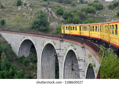 LATOUR DE CAROL - SEPTEMBER 4, 2018: The small yellow train of the Pyrenees crossing a beautiful mountain landscape
