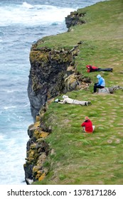 Latrabjarg / Iceland - June 10, 2010: Bird watchers sit and lie on edge of Latrabjarg dramatic steep sea bird cliffs to view puffins.Cliffs are of international importance for breeding sea birds.
