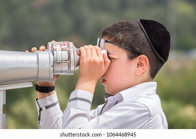 LATRUN, ISRAEL - APRIL 3, 2018: Orthodox Jewish boy look through a viewing binocular