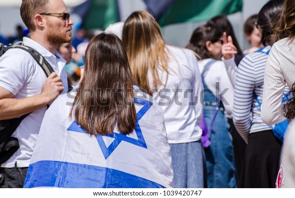 LATRUN, ISRAEL - MAY 02, 2017: The patriotic girls wrapped in Israeli flags celebrate Israel Independence day