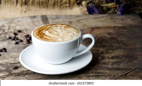 Latte art and cappuccino with leaf and flowers made from milk on the wood table with roasting coffee beans. Beverage and breakfast menu with hot coffee at the cafe shop. A cup of capuccino art.