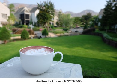 latte art coffee with beautiful view in green yard and mountain.