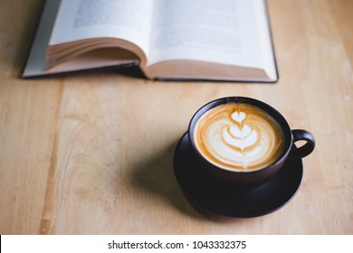 Latte art coffee in black cup with open book on wood table in coffee shop