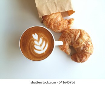 Latte art coffee with croissant so delicious on white
