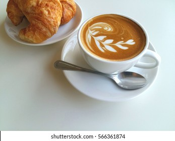Latte art coffee and croissants so delicious on white