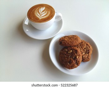 Latte art coffee so delicious with cookies on white