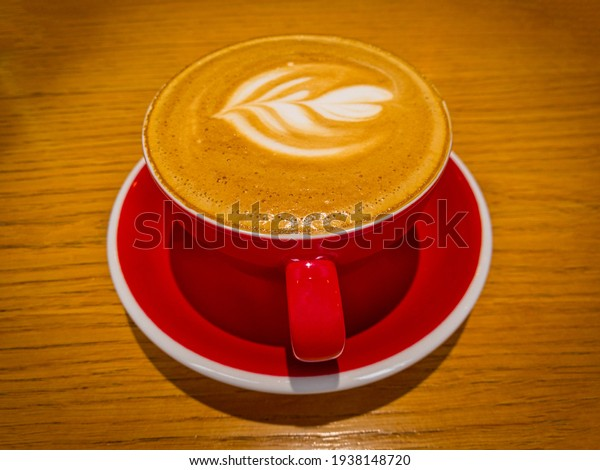 Latte Art On Froth. Hot latte coffee on wooden table. Morning with a red cup of cappuccino. Art and craft coffee.
