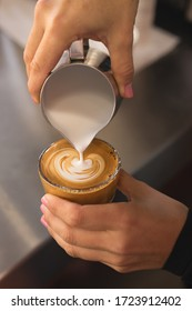 Latte art in a shape of heart by a barista