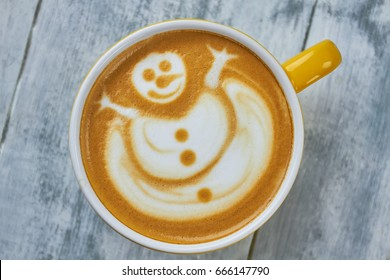 Latte art snowman. Coffee cup, top view.
