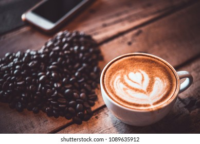 Latte arts coffe. White cup of hot coffee on wooden table with heart shape of coffee beans. Cafe with barista art concept.