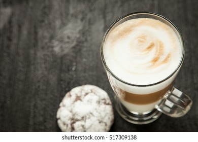 latte cappuccino with cookies on a black background