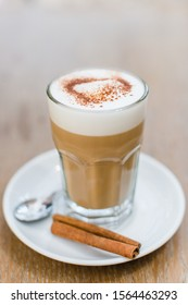 Сoffee latte with cinnamon in a glass on a wooden table