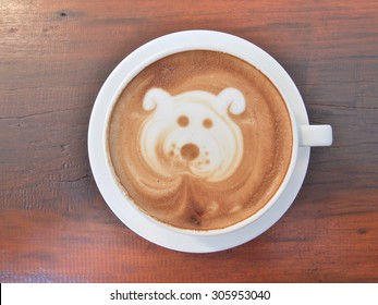 """Latte Coffee art """"Dog Face"""" on the wooden desk."""