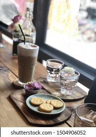 Latte coffee and biscuits With water in the coffee shop.