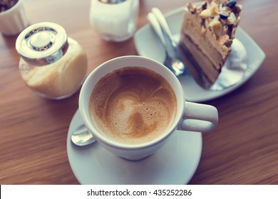 Latte coffee with coffee cake  in coffee shop in vintage tone color,view from the top.