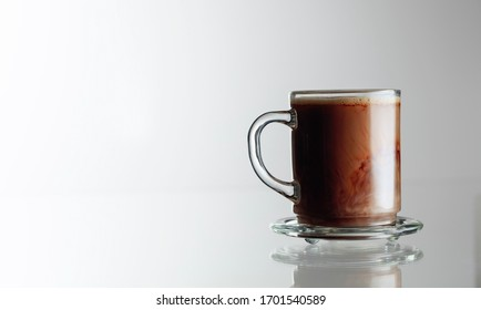 Latte coffee in glass cup on a glass table. Copy space.