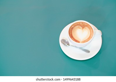 Latte coffee is a heart shape. Aqua (color) background