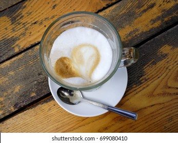 Latte coffee with heart shape on old wooden table, top view