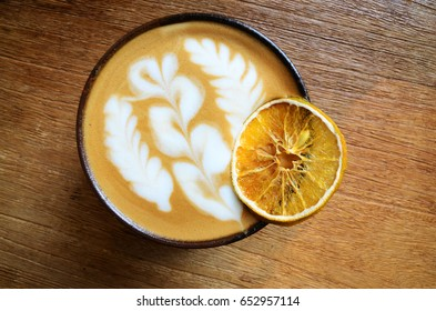 Latte coffee with a slice dried citrus