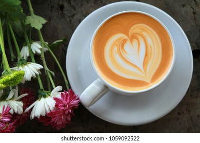 Latte coffee in white cup with flower on wooden desk in top view