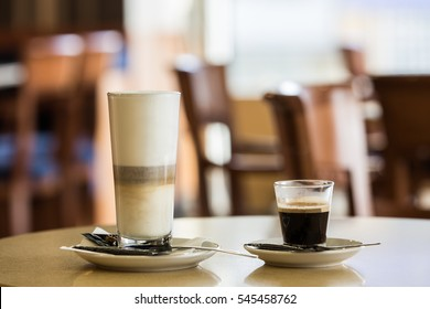 Latte and espresso in glass cups on a table in a caffe