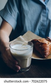Latte glass cup with croissant on dark retro wood background.