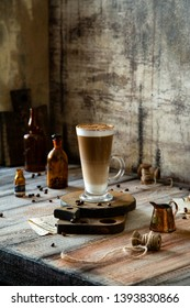 Latte glass with layered latte, cappuccino or mocha on wooden boards stand on grey rustic table with milk saucer, spool of thread, vintage bottles, beans opposite concrete wall